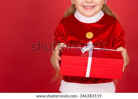 The biggest gift of all. Cropped studio shot of a little kid dressed like Santa Claus holding Christmas present and smiling widely against red background - stock photo