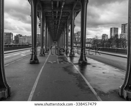 The Bir Hakeim bridge in Paris France has a bicycle lane running down the middle with automobile traffic on each side and a public transportation train tracks above. - stock photo