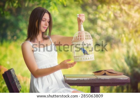 The bird cage / Beautiful young women holding a cage with a bird, with custom white balance, color filters, soft focus effect, and some fine film grain added - stock photo