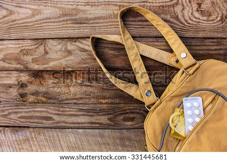 The birth control pill and condom falls out of pocket with handbags on wooden background. Toned image.   - stock photo