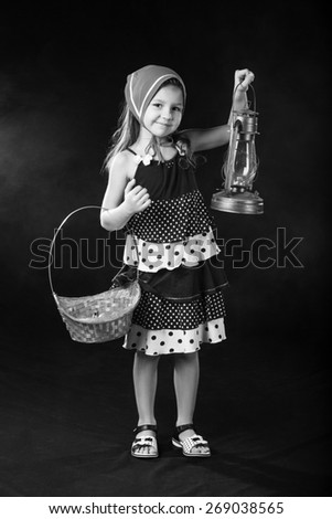 The black-and-white portrait of beautiful little girl in dress and red scarf standing with basket and oil-lamp  - stock photo