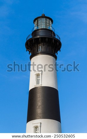 The black and white striped tower of the Bodie Island LIghthouse stands against a deep blue North Carolina sky.