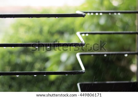 The black bars with raindrops on a rainy day in a garden of hotel. - stock photo