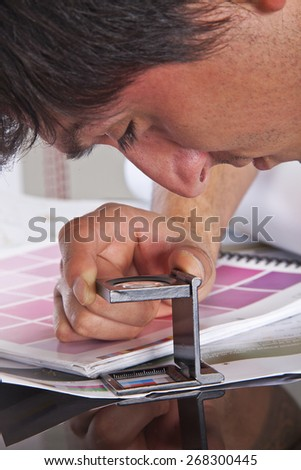 The black glass standing on a leaf of the test print and pantone. Man working in the printing industry. - stock photo