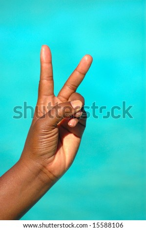 The black hand of an African American woman showing the symbolic victory sign after success where she was the winner - stock photo