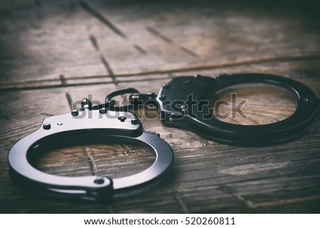 the black handcuffs on wooden background. criminal justice