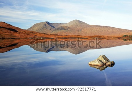 The Black mount mountain range on a very calm day. Just as all the mist lifted it revealed this mirror image on Loch Ba, Rannoch moor. - stock photo