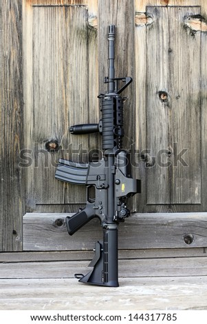 "The Black Rifle. 14,5"" AR-15 assault carbine (M4A1) with holographic sight against an old wooden door. Vertical composition. - stock photo"