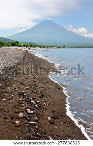The black sand beach, Amed beach with the valcano Agung in the eastern part of Bali, Indonesia - stock photo