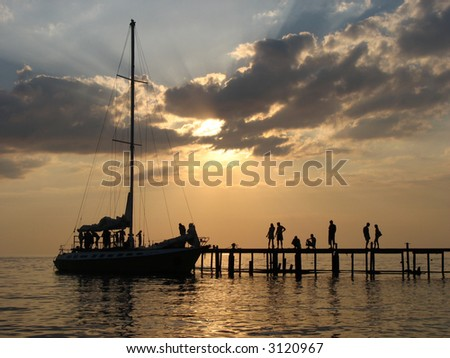 The Black sea, the sunset, and the silhouette of the yacht near the mooring line.