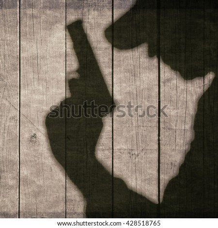 The Black Shadow Of A Man With A Handgun On The Wooden Wall. Black Armed Male Silhouette On The Wooden Fence. - stock photo