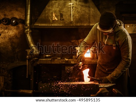 The blacksmith with brush handles the molten metal on the anvil in smithy.