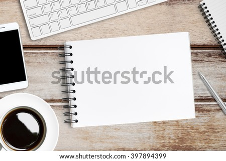 The blank note book page is open in the middle of wood office table.  - stock photo