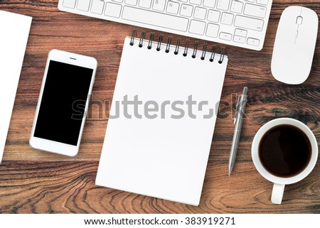 The blank page of notebook is showing on the wood office table with a lot of supplies on it. Top view. The blank notebook can be put some texts or images. - stock photo