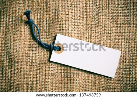 the blank price tag label on burlap background - stock photo