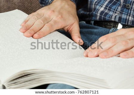 The blind man was reading a book written on Braille. Touch your finger on the braille code. A book with Braille text.