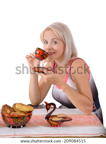 The blonde drinks tea  from painted tea things - stock photo