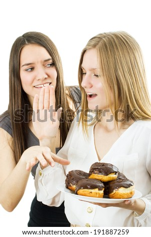 The blonde forbids the brunette to take appetizing cake. The isolated background - stock photo