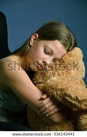 The blonde girl put her head on the big teddy bear and closed her eyes. She is cuddling the soft fluffy toy close.