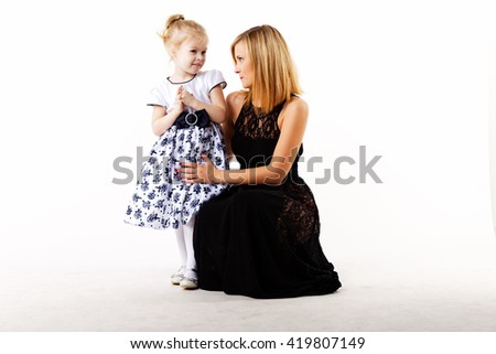 The blonde in a black evening dress with a little girl blonde. Mother with daughter. White background. - stock photo