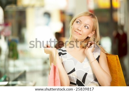 The blonde in shop with purchases looks aside - stock photo