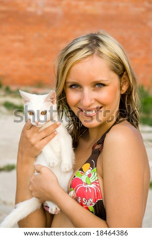 The blonde with a kitten on a beach