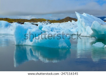 The blue and emerald icebergs and ice floes floating in the gulf Yokulsarlon in Iceland. Sunrise. - stock photo