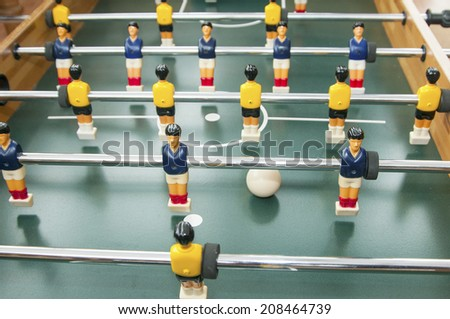 the blue and the yellow team are ready for battle in the table football bar sport