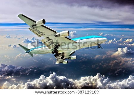 The blue and white wide-body aircraft. Plane is flying against the backdrop of a cloudy sky. - stock photo