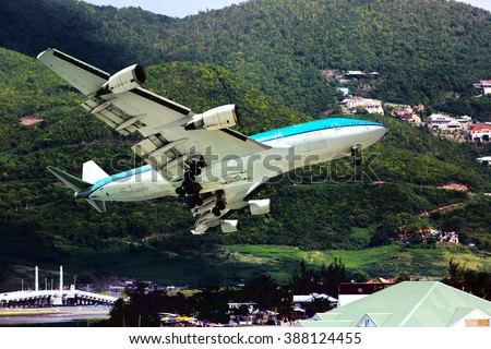The blue and white wide-body aircraft. Plane is flying against the backdrop of a huge mountains. - stock photo