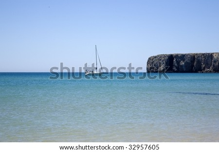 The blue beaches of southern Portugal, the Algarve. Martinhal beach in a summer morning, with a sailing ship passing by - stock photo