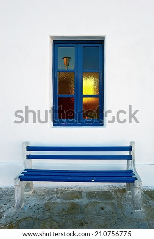 The blue bench and the stained-glass window of the unidentified building in Mykonos, Greece - stock photo
