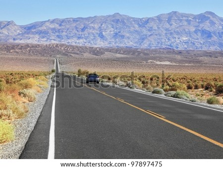 The blue car driving through the road, crossing Death Valley in the USA. The low dry bushes and mountains - stock photo