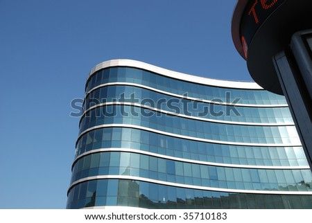 The blue facade of a modern building with running illuminated signs - stock photo