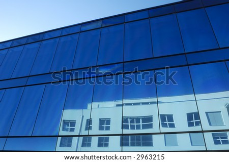 The blue glass facade of an office block with the distorted reflection of a neighbouring building showing in the windows.
