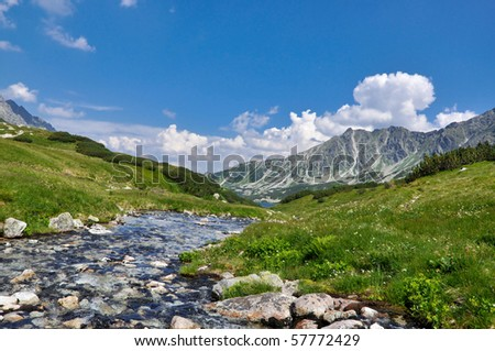 The blue lake and surrounding mountains - stock photo