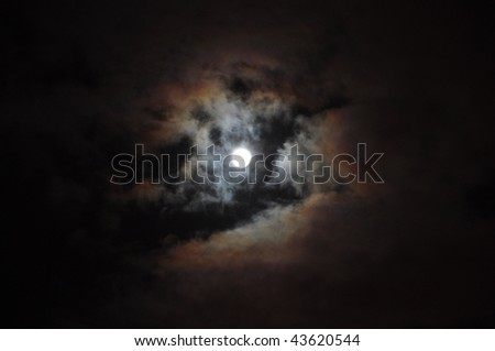 The blue moon in darkness on a background of clouds - stock photo