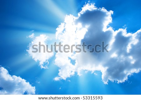 The blue sky and sun beams shining through clouds - stock photo