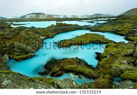 The blue water between the lava stones covered with moss just outside the Blue Lagoon resort of Iceland - stock photo