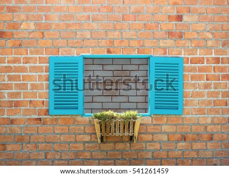 The blue wooden window on a brick wall.