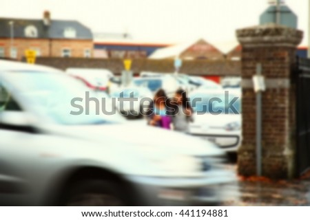 The blurry focus scene of mother and daughter wait to cross the road represent the road safety and transportation concept related idea.