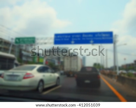 The blurry focus scene of traffic route information banner above highway through the car windscreen represent the car and transportation concept related idea. - stock photo