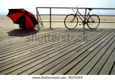The boardwalk at Coney Island in New York with sun shade and bike - stock photo