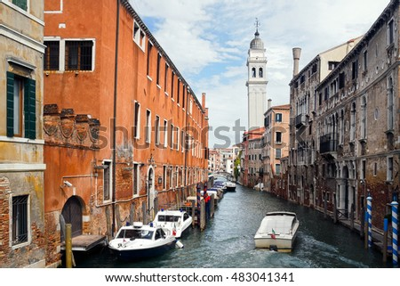 The boat floating on the channel of Venice  (Venezia) with old buildings, boats and the leaning belfry tower of San Giorgio dei Greci, Italy
