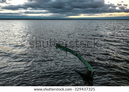 The boat flooded with waves and rains on an autumn decline - stock photo