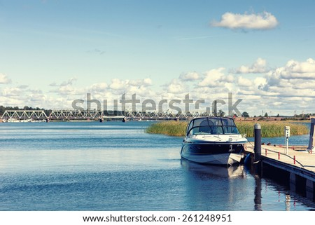 The boat is at the dock on the river against the background of the railway bridge across the river on a summer day. Latvia, Baltic - stock photo