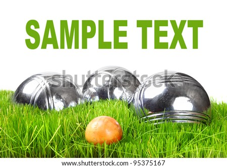 The bocce balls on a green grass. Picture with space for your text. - stock photo