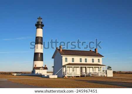 The Bodie Island lighthouse and keeper's quarters at the Cape Hatteras National Seashore against a bright blue sky