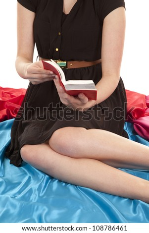 The body of a woman reading a red book. - stock photo
