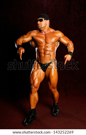 The bodybuilders back on a dark background. - stock photo